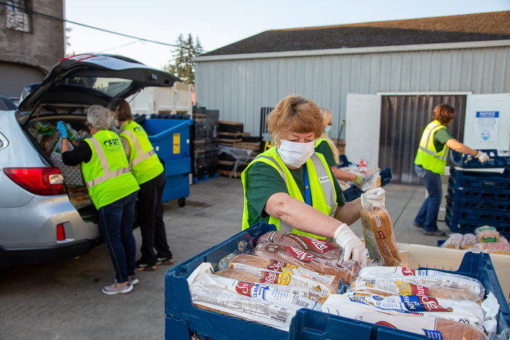 Volunteers load food in cars