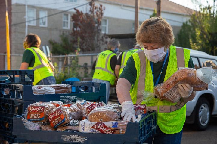Volunteers load food in cars